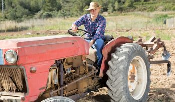 Farmer_sitting_on_a_tractor_looking_at_the_camera